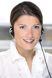 Call center worker. A portrait of a pretty girl in the call center over light background Stock Photography
