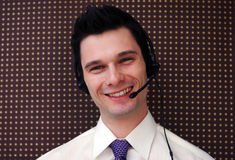 Call center worker. Friendly male call center operator takes a call from a client Stock Photos