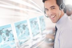 Call center worker using futuristic interface hologram. Smiling at camera in office Royalty Free Stock Photography