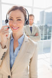 Call centre agent smiling with colleague behind her Stock Image