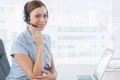Call centre agent wearing headset at her desk Stock Images