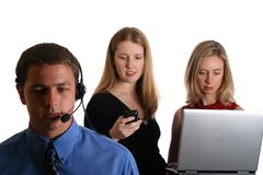 Call centre and business women. A call centre agent or secretary stands in the foreground while two business women complete a transaction in the background using Stock Photography