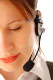 Call centre executive. Cropped image of a yound attractive business woman with headset looking down and smiling, isolated over white background Stock Images