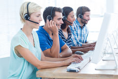 Call centre workers on their laptops. Happy call centre workers on their laptops Royalty Free Stock Images