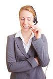 Call with headset. Happy blond business woman using a headset royalty free stock photo