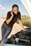 Call for help. Young woman stands next to the car with bonnet up and calls for help Royalty Free Stock Photography