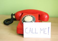 Call me. One old, red telephone and a note on a desk stock images