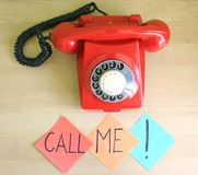 Call me. One old, red telephone and a note on a desk royalty free stock images