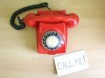 Call me. One old, red telephone and a note on a desk Stock Photos