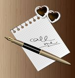 Call me. On a wooden surface lies a pen, a note with the words  call me and two chocolates in the shape of a heart Stock Photo