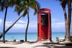 Call Me. Red Phone booth on the Caribbean beach of Antigua inviting a tropical holiday phone call Stock Photography