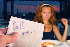 Call me... Message on napkin in hand against pretty girl Royalty Free Stock Photos