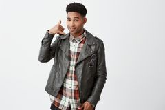 Call me, babe. Portrait of beautiful cheerful young black-skinned african men with curly black hair in leather jacket Royalty Free Stock Image