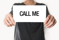 Call me. Female in black shirt showing or holding a card Royalty Free Stock Images