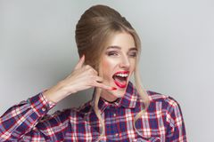 Call me! funny beautiful blonde girl in pink checkered shirt, co. Llected updo hairstyle, red lips and makeup standing and looking at camera with calling gesture stock photography