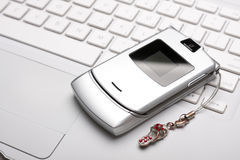 Call me! Mobile phone on a white laptop. Silver mobile phone on a white laptop. Top view Royalty Free Stock Images