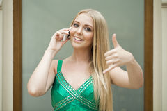 Call Me. Sexy young woman in green dress making a call me gestur Stock Images