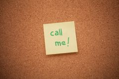 Call me sticky note. A call me sticky note on a cork board stock images