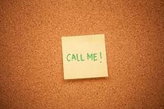 Call me sticky note. A call me sticky note on a cork board stock photo