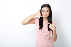 Call me. Woman showing sign and smiling on white. Royalty Free Stock Image