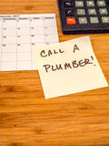 Call a plumber, Post it reminder, copy space Royalty Free Stock Photo