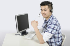 Call service worker. Young Asian man seated at a desk wearing a telephone headset Royalty Free Stock Image