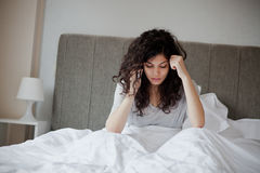 Call in sick. Woman calls in sick in the morning from her bed stock photography