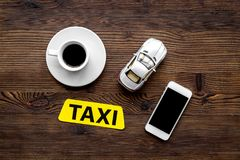 Call a taxi with mobile app and cup of coffee wooden table background top view copyspace. Call a taxi with mobile app and cup of coffee on wooden table Royalty Free Stock Photos