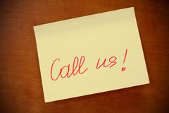 Call us!. Wooden board  with yellow  sticky note call us Royalty Free Stock Photography