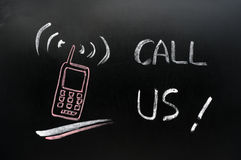 Call us. Symbol of a cellphone on blackboard Royalty Free Stock Photos