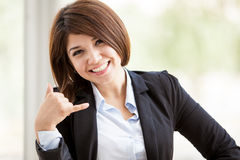 Call us now!. Gorgeous Hispanic business woman asking for you to call using a hand sign Royalty Free Stock Images
