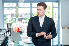 Call Waiting. Confident and successful businessman standing in a Stock Image