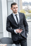 Call waiting. Young businessman in formal wear holding a cell ph Stock Image