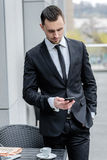 Call waiting. Young businessman in formal wear holding a cell ph Royalty Free Stock Photo
