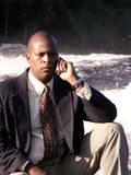Call in the willd. Business man in a suit with cell phone sitting on a rock in front of a river royalty free stock image