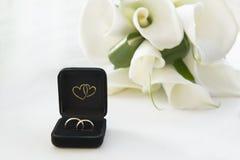 Callas и 2 золотых обручального кольца на белой предпосылке Стоковое Фото