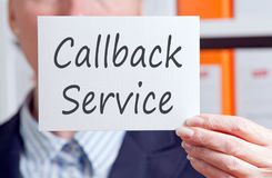 Callback Service - Businesswoman with sign in the office. Callback Service - Businesswoman holding sign with text in the office stock photo