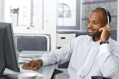 Callcenter agent with headset. Callcenter agent sitting at office desk, working on phone with headset Royalty Free Stock Image