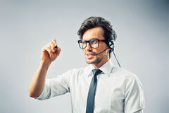 Operator with headset. Callcenter operator giving advice via telephone and writing copyspace Stock Photos