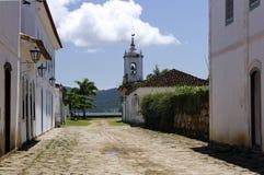 Calle abandonada del guijarro con la iglesia y el mar Imagen de archivo libre de regalías