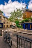 Calle acogedora con el molino viejo y bici en Montmartre cuarto en París foto de archivo libre de regalías