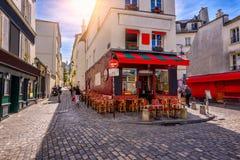 Calle acogedora con las tablas de café en Montmartre cuarto en París foto de archivo