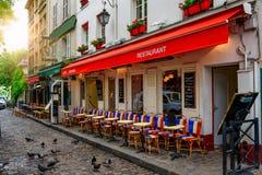 Calle acogedora con las tablas de café en Montmartre cuarto en París, fotos de archivo