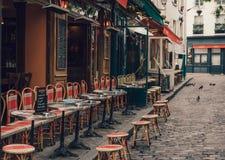 Calle acogedora con las tablas de café en Montmartre cuarto en París foto de archivo libre de regalías