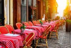 Calle acogedora con las tablas de café en Montmartre cuarto en París fotos de archivo