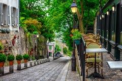 Calle acogedora con las tablas de café en Montmartre cuarto en Pari imagenes de archivo
