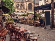 Calle acogedora con las tablas de café en París imagen de archivo