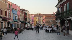 Calle animada en Burano con la gente en cafés al aire libre, Italia almacen de video