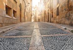 Calle antigua con el puente gris del pavimento de la ciudad antigua Tarragona de España el día soleado fotografía de archivo