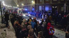 Calle apretada de Tallinn Harju Después de los Años Nuevos celebración, impulsiones de la ambulancia a través de la muchedumbre d